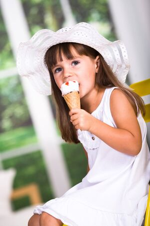 young girl eating an ice cream photo