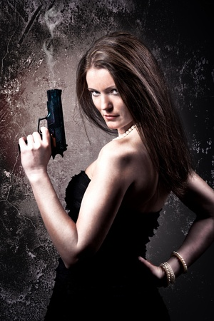 studio portrait of young a woman with a gun Imagens