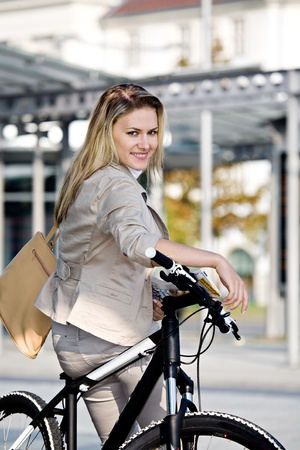 business activity: A young woman travelling on public transport with bike Stock Photo