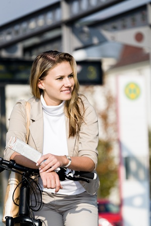 A young woman travelling on public transport with bike Imagens