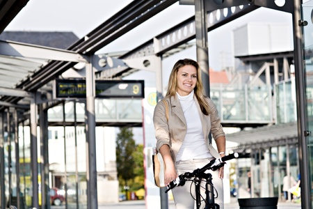 A young woman travelling on public transport with bike photo