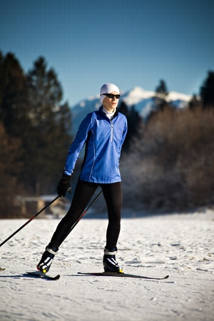 A woman cross-country skiing in the Alps photo