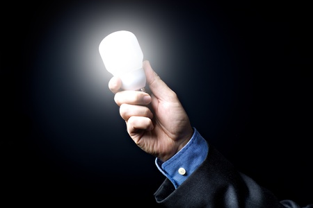 Symbolic picture with mans hand and a shining light bulb Stock Photo