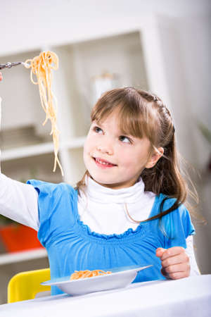 young girl eating spaghetti at home. A studio shoot. photo