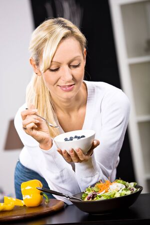 a young woman eating yogurt in the kitchen photo