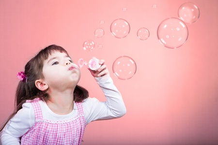 blowing bubbles: a little girl blowing soap bubbles