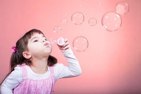 burbujas de jabon: una niña soplando pompas de jabón Foto de archivo