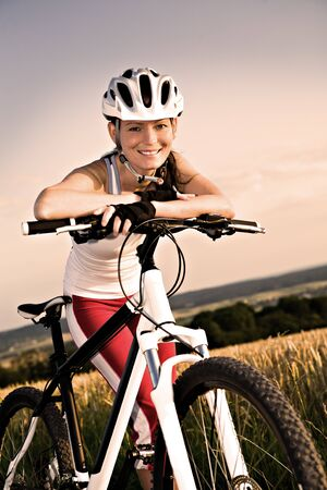 woman bike: A cycling woman in front of rural landscape