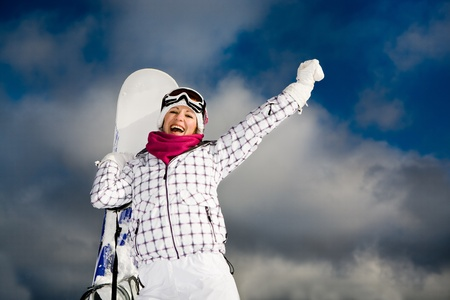 A young woman snowboarding in the Alps, an outdoor shoot. Imagens