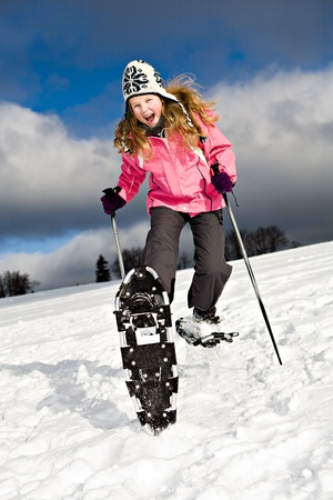 snowshoes: A young girl running with snowshoes in the Alps.