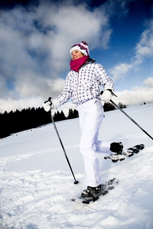snowshoes: A young woman running with snowshoes in the Alps.
