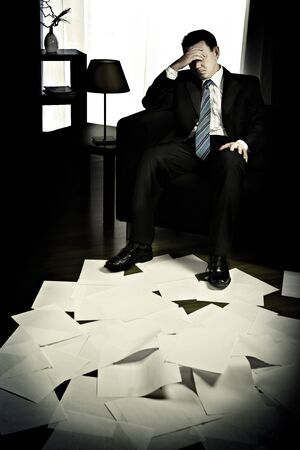 Symbilic picture of a depressed businessman with stack of documents. photo