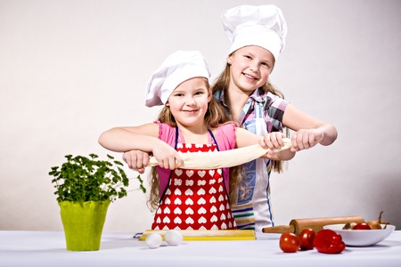 young girls baking cakes in the kitchen photo