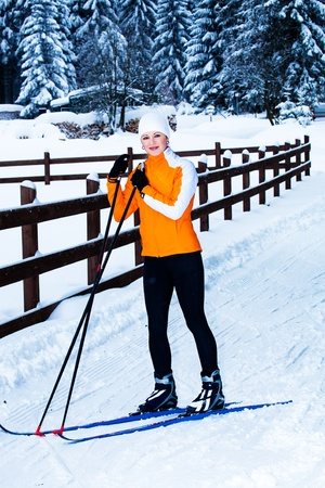 young woman cross-country skiing in a forest photo
