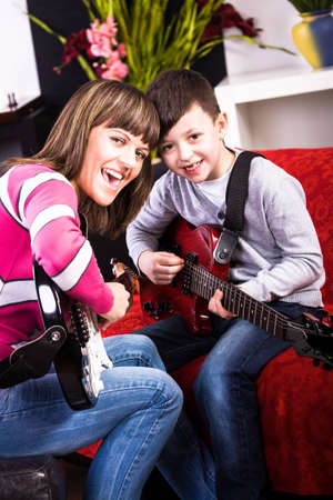 boy playing guitar: young woman and a boy playing guitar in the own home Stock Photo