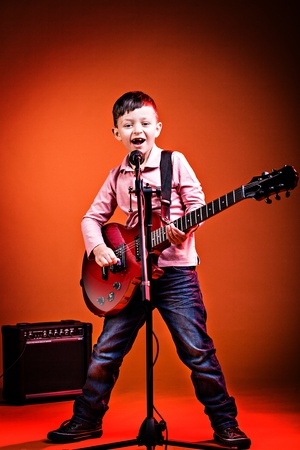 portrait of young boy with a guitar on the stage Stock Photo