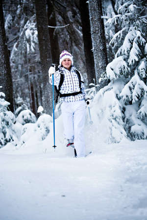 young woman hiking  in a snowy forest photo