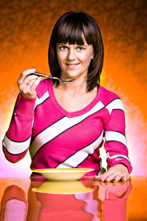 a young woman eating soup in front of color background photo