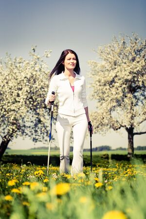 nordic walking: a young woman making nordic walking. outdoor shoot.