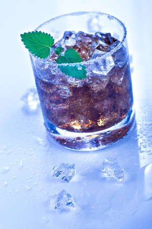 a glas with a rum, ice and lime cocktail photo