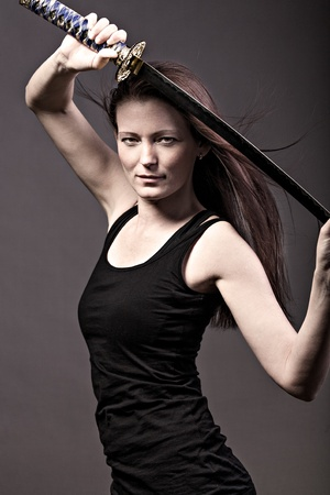 studio portrait of a young woman with a samurai sword photo