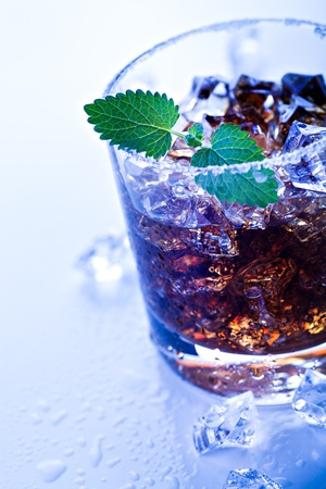 glas: a glas with a rum, ice and lime cocktail