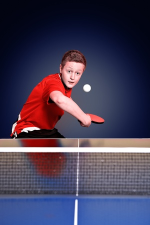 a boy playing ping-pong (table tennis) photo