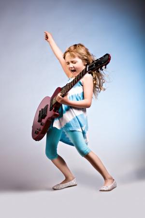 gitara: Portret mÅ'odej dziewczyny z gitarÄ… na scenie Zdjęcie Seryjne