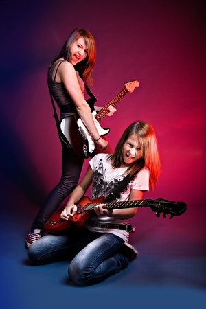 portrait of two young girls with a guitar on the stage photo