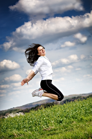a young jumping woman in front of rural landscape photo