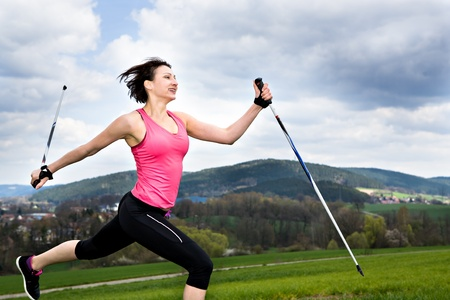 a young woman making nordic walking. outdoor shoot. photo