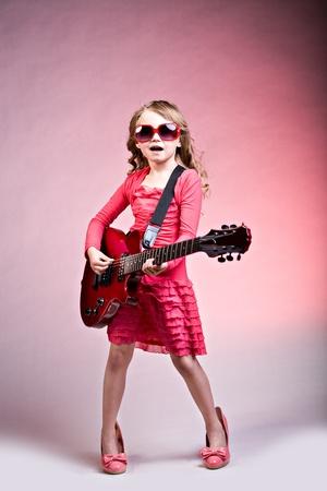 enfant qui joue: portrait de jeune fille avec une guitare sur la scène