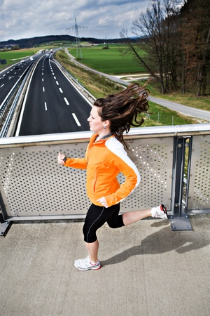 A woman jogging in front of cross country photo