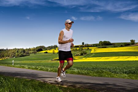 a young man jogging through the fields Imagens - 13548635