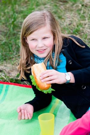 picknick: teeny girl with sandwich at picknick