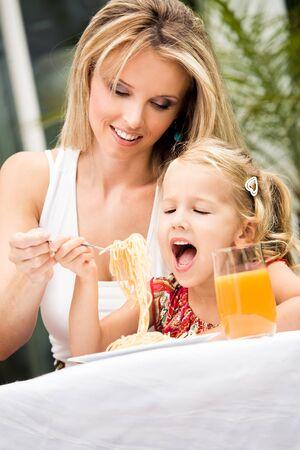 girl eating spaghetti in a garden photo