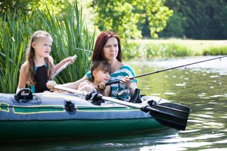 family fishing on lake at summer photo