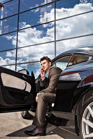 young businessman phoning at  a modern car photo