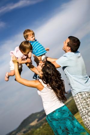gemelos niÑo y niÑa: joven familia en la pradera en el día soleado Foto de archivo