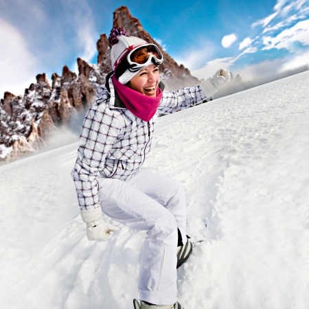 A young woman snowboarding in the Alps, an outdoor shoot. Stock Photo