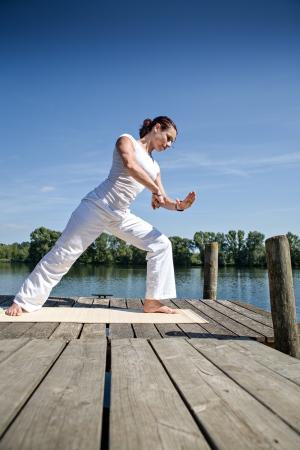 young woman making tai chi exercise at a lake Imagens - 15412163