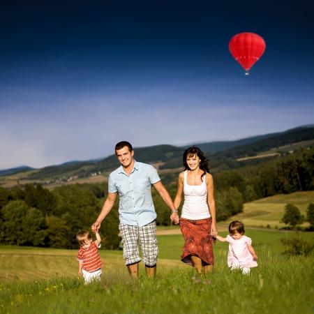junge Familie auf der Wiese am sonnigen Tag