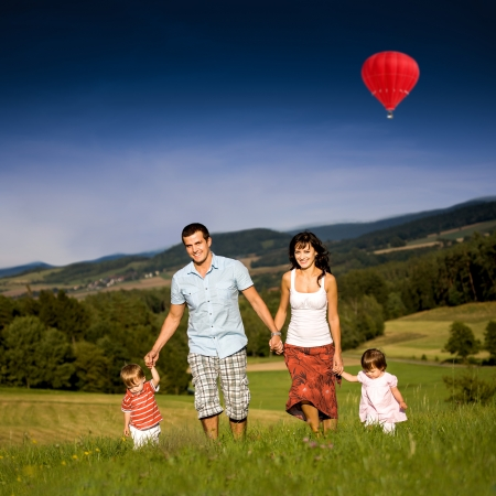 outdoor activities: young family on the meadow at sunny day Stock Photo