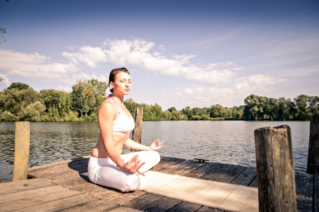 young woman making yoga exercise at a lake photo