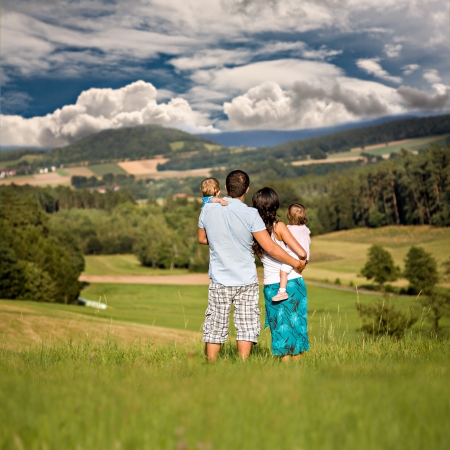 young family on the meadow at sunny day photo