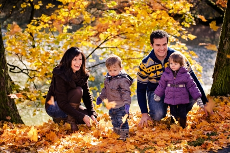 family fall: portrait of a young family in the autumn park Stock Photo