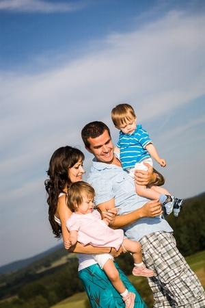 young family: young family on the meadow at sunny day Stock Photo