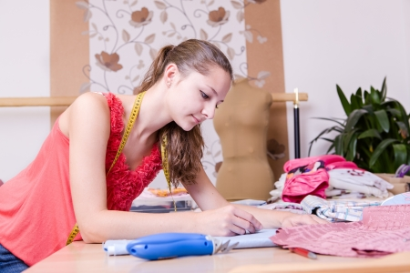 a young female couturier in the workroom photo