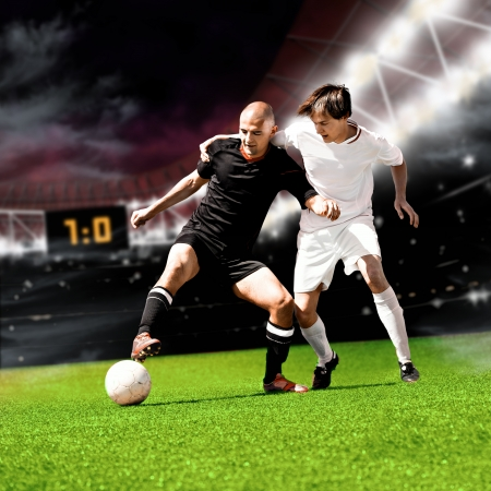 soccer grass: two football players from opposing team on the field