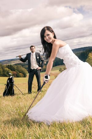 a newly married couple with golf accessories